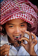 Tarantula seller Sok Khun takes a dainty bite of one of the deep-fried tarantulas that she sells at a roadside market, Kampong Cham Province, Cambodia.(Man Eating Bugs: The Art and Science of Eating Insects page 48. See also cover of book) .