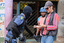 JOHANNESBURG, SOUTH AFRICA - APRIL 18: A man is searched by a SAPS officer during a South African Police Service (SAPS) Metro Police and Army supported patrol in Rockey Street, Yeoville. Random searchs and social distancing measures on April 18, 2020 in Johannesburg South Africa. Under pressure from a global pandemic. President Ramaphosa declared a 21 day national lockdown extended by another two weeks, mobilising goverment structures accross the nation to combat the rapidly spreading COVID-19 virus - the lockdown requires businesses to close and the public to stay at home during this period, unless part of approved essential services. (Photo by Dino Lloyd)