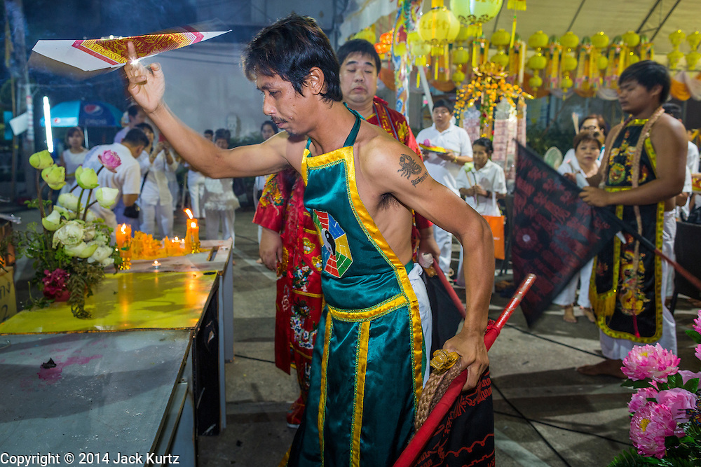 01 OCTOBER 2014 - BANGKOK, THAILAND: A firewalker blesses himself with flames before the firewalking at Wat Yannawa (also spelled Yan Nawa) during the Vegetarian Festival in Bangkok. The Vegetarian Festival is celebrated throughout Thailand. It is the Thai version of the The Nine Emperor Gods Festival, a nine-day Taoist celebration beginning on the eve of 9th lunar month of the Chinese calendar. During a period of nine days, those who are participating in the festival dress all in white and abstain from eating meat, poultry, seafood, and dairy products. Vendors and proprietors of restaurants indicate that vegetarian food is for sale by putting a yellow flag out with Thai characters for meatless written on it in red.     PHOTO BY JACK KURTZ