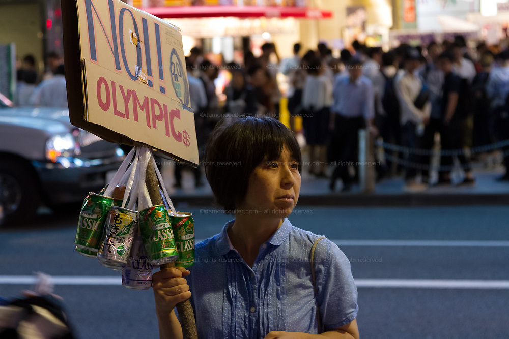 """A woman holds a sign reading """"No Olympics"""" at a  small protest against the staging of the Olympic Games in Shinjuku, Tokyo, Japan Friday June 30th 2017. Though mostly popular with the Japanese population he staging of the 2020 Olympic Games in Tokyo is felt by some to be a waste of money when the economy is bad, causing increasing poverty rates and with problems in the Tsunami damaged North East coast still not fully resolved."""
