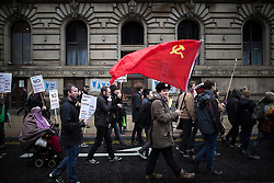 """© Licensed to London News Pictures . 05/12/2015 . Manchester , UK . A man carries a Soviet Union flag along the march route . Approximately one hundred anti-war protesters march through central Manchester against Parliament's decision to vote in favour of bombing against """" ISIS """" , in Syria . Photo credit : Joel Goodman/LNP"""