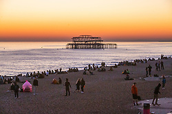 © Licensed to London News Pictures. 26/02/2019. Brighton, UK. Members of the public take to the beach in Brighton and Hove to watch the murmurations as thousands of starlings take to the sky over the Brighton Palace Pier before descending to roost for the night on the legs underneath the Brighton and Hove seaside pier. Photo credit: Hugo Michiels/LNP