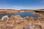 Basalt cliffs tower over one of the Sage Lakes, located in the Columbia National Wildlife Refuge near Othello, Washington. The wildlife refuge is home to numerous lakes, even though the area receives less than eight inches of rain per year.