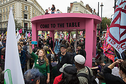 London, UK. 23rd August, 2021. Environmental activists from Extinction Rebellion assemble around a giant table used to block roads in the Covent Garden area during the first day of Impossible Rebellion protests. Extinction Rebellion are calling on the UK government to cease all new fossil fuel investment with immediate effect. Credit: Mark Kerrison/Alamy Live News