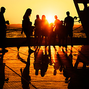 People enjoying the sunset on a warm summer evening at the Sun Salutation (on the ground) in Zadar, Croatia. Designed by architect Nikola Basic, it harvests sun during the day and puts on a light show in the evening using the rhythm of the waves.
