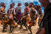 Women dancing and jumping at a Hamer tribe bull jumping ceremony, which is a rite of passage to initiate a boy into manhood. Omo Valley, Ethiopia.