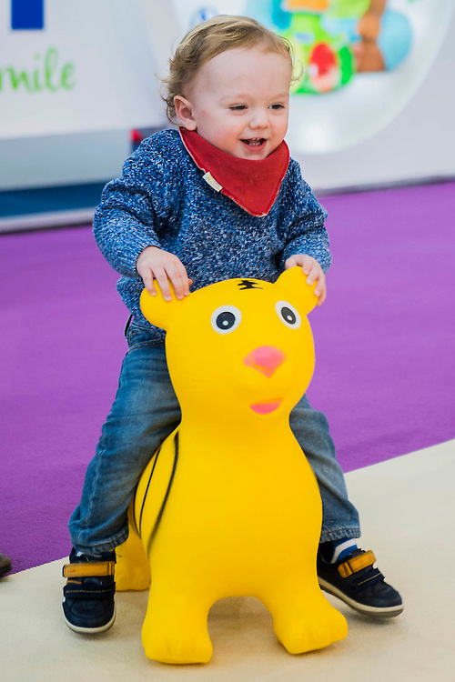 Siblings aged 4 and 18 months play on the Artstraws stand - The annual London Toy Fair, the trade show for the toy and games industry, takes place at Olympia.