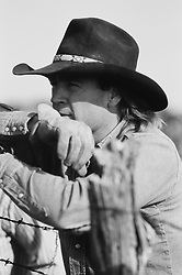 Cowboy leaning on a barbed wired fence looking out, b&w