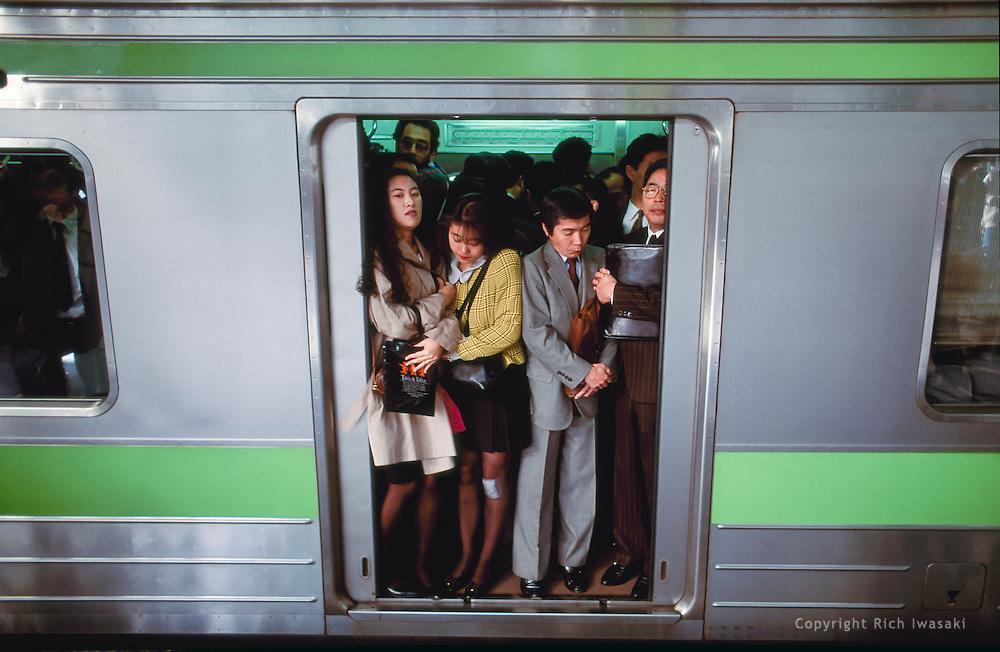 Morning commuters crowd into a full train at Shinjuku station during rush hour, Shinjuku district, Tokyo, Japan