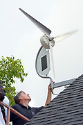 "Installation of a residential wind turbine is filmed for an episode of the DIY network show ""This New House"". Bob Hayes of Prevailing Winds and his crew install a Dyocore SolAir 800 I wind turbine which integrates two small solar panels into its design and is capable of producing up to 800 Watts at 12 mph. The two solar panels produce up to 45watts. Redondo Beach, Ca, USA"
