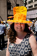 """New York, NY - April 16, 2017. A woman at New York's annual Easter Bonnet Parade and Festival on Fifth Avenue wears a hat covered in cheese puffs, and bearing a sign that reads """"Not my cheese puff president bonnet full of air, cheezy, + bad for us."""""""