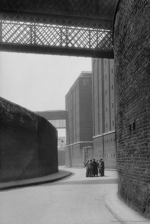Group on a Street Surrounded by Brick Walls, London, 1933