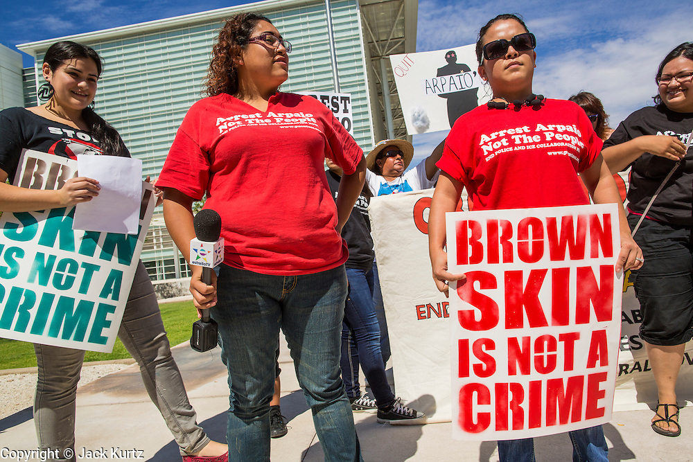 """19 JULY 2012 - PHOENIX, AZ: LETICIA RAMIREZ (center) and NATALLY CRUZ (right) both from Puente, a human rights organization, speak out against Maricopa County Sheriff Joe Arpaio in front of the US Courthouse on the first day of a class action lawsuit, Melendres v. Arpaio in Phoenix Thursday. The suit, brought by the ACLU and MALDEF in federal court against Maricopa County Sheriff Joe Arpaio, alleges a wide spread pattern of racial profiling during Arpaio's """"crime suppression sweeps"""" that targeted undocumented immigrants. U.S. District Judge Murray Snow granted the case class action status opening it up to all Latinos stopped by Maricopa County Sheriff's Office deputies during the crime sweeps. The case is being heard in Judge Snow's court.   PHOTO BY JACK KURTZ"""