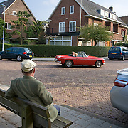 Nederland Rotterdam 20 September 2009 20090920 ..Dure wijk Kralingen, oudere man zit op een bankje in het zonnetje. Op de achtergrond passeert een stel in een rode  cabriolet.  .City of Rotterdam, area Kralingen, expensive district. Old man observes rich couple passing by in cabriolet.                            ..Foto: David Rozing