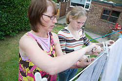 Teenage girl helping her mother hang out the washing,