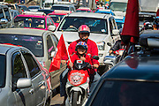 08 MAY 2013 - BANGKOK, THAILAND: Red Shirts on a motorcycle during a motorcade to the Thai parliament building. A splinter group of the Red Shirts, Thai supporters of exiled Prime Minister Thaksin Shinawatra, have besieged the Thai Constitutional Court for the last three weeks calling for the resignation of the justices, who have indicated they might oppose a proposed constitutional reform which would grant amnesty to people convicted of political crimes since 2007. This would probably include Thaksin. The justices have refused to step down. Wednesday the protesters moved their protest to the Thai Parliament, which is largely powerless to intervene.   PHOTO BY JACK KURTZ