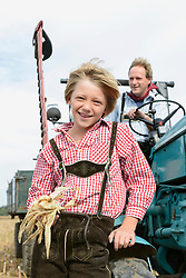 Father and son with tractor in cornfield, Bavaria, Germany