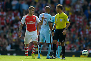 Arsenal's Jack Wilshere makes a point to Referee Mark Clattenburg  .Barclays Premier league match, Arsenal v Manchester city at the Emirates Stadium in London on Saturday 13th Sept 2014.<br /> pic by John Patrick Fletcher, Andrew Orchard sports photography.
