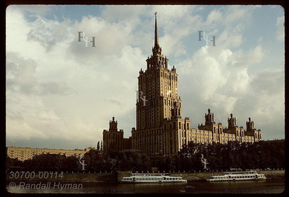 Hotel Ukraina-one of seven skyscrapers Stalin erected in the 50s, looms over boats on Moscow River Russia