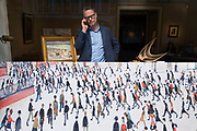 Man inside an art gallery on Bond Street concentrating while on a phone call while outside a print of a Lowry painting adorns the exterior in London, England, United Kingdom. Bond Street remains one of the most exclusive shopping, fashion and art streets in the capital.