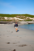 Woman walking on sandy beach at Bagh a Deas, South Bay, Vatersay island,Barra, Outer Hebrides, Scotland, UK