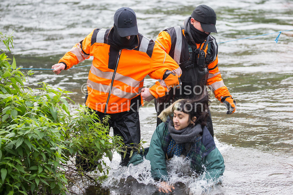 Denham, UK. 5th November, 2020. HS2 security guards push a female anti-HS2 activist into the river Colne at Denham Ford during bridge building works for the HS2 high-speed rail link on the first day of the second national coronavirus lockdown. Prime Minister Boris Johnson has advised that construction work may continue during the second lockdown but those working on construction projects are required to adhere to Site Operating Procedures including social distancing guidelines to help prevent the spread of COVID-19.