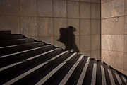 The shadow of a lonely figure descends steep steps. The person is out of sight but we see their form against the panelling of 1980s architecture, located on the south side of London Bridge in the London borough of Southwark.