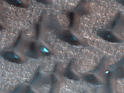 These dark sand dunes in the North polar region, basking in the sunshine of late spring, have shed most of their seasonal layer of winter ice. MRO.