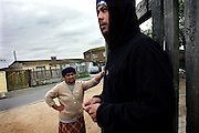 Youngsters on the streets of the impoverished neighbourhood of Heideveld, Cape Town, RSA. Francis, a woman living in the area from 40 years is on the back; she has witnessed and has been threatened by the wave of violence affecting these communities. Her grandson, who was part of a gang in the area has been shot three times in front of her house by the common drive-by-shootings carried on by rival gangs in the neighbouring areas. Being in so close contact with members of gangs and criminal activity, youngsters are those who are most tempted to join a gang, which most of the time is also probably composed by friends and others living in the community. Making errands or favours to gang members is also common to the younger kids in these areas which are lured by the apparently easy gains deriving from the activity.  With extremely high rates of unemployment, poor resources and too little authority control, ghettos as Heideveld are the best places for gangs to grow in activity and businesses. Targeting mostly young people from their area to carry on the 'dirty job', gangs in the Western Cape, and South Africa are an endemic problem in continuous increase in the years after the radical apartheid governmental system. 'Coloured' communities have lost almost all their help from a government that now is concentrated on empowering black communities instead. Segregated into ghettos and without state grants or development activities, people in these communities are sometimes forced to join a gang or dealing drugs also to provide for their own family. Young gangster are also used for the worst crimes by the fact that, being still under 18 years old, they would face shorter sentences if caught. Drug abuse between kids as young as 12 is not uncommon, especially crystal meth, mandrax and marijuana.