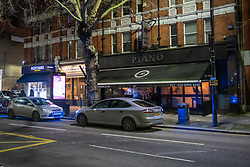 © Licensed to London News Pictures. 29/01/2021. London, UK. Unmarked police vehicles outside the Piano Restaurant in Chiswick. Police were called to the Piano Restaurant on Chiswick High Road on the evening of Friday 29th after reports of a large gathering. Police forced entry through a rear door which lead to many at the gathering to flee through the main entrance at the front of the restaurant. A number of people were detained for a short period including one person held in a police van. Photo credit: Peter Manning/LNP