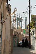 Iran. Qom , Women in tchador in a street, the big mosque of Qom in the distance