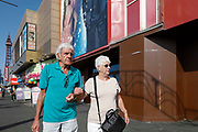An elderly couple walk arm in arm up the promenade with the world famous Blackpool Tower in the background as temperatures in the country are expected to soar this week on 7th September, 2021 in Blackpool, United Kingdom. Temperatures in the UK are predicted to soar to highs of 29 degrees celsius, coinciding with a rise in daycation and staycation domestic tourism in the country as a result of Covid-19 precautions that make foreign travel increasingly costly and difficult.