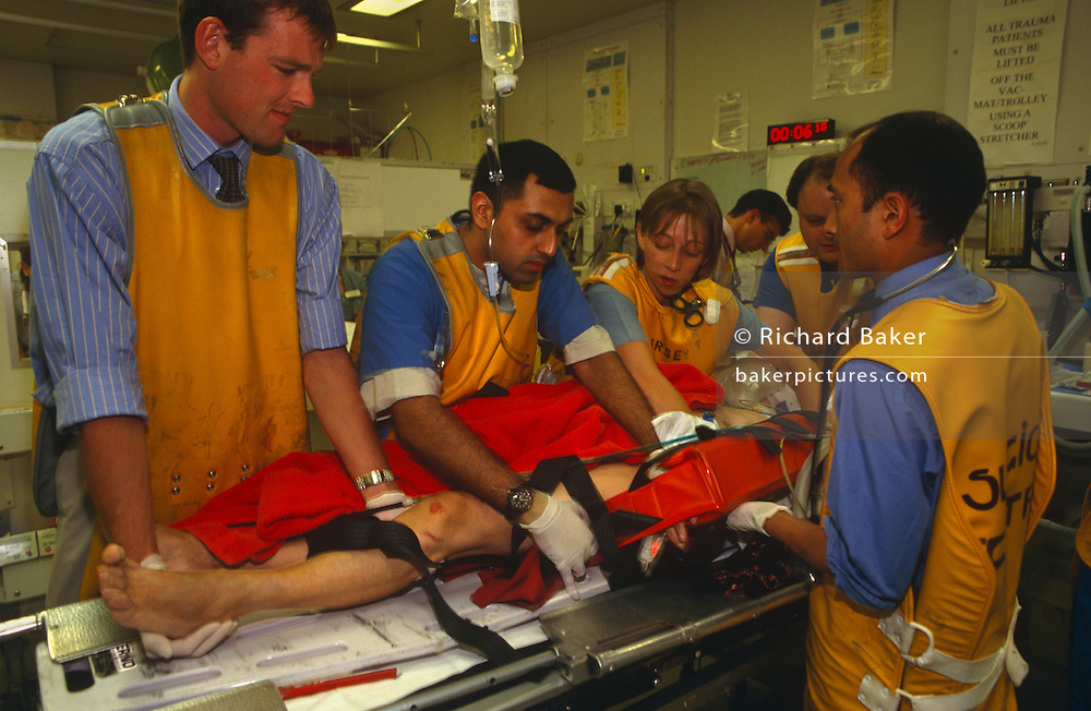 "At the Royal London Hospital, accident and emergency (A & E) medical staff wearing radiation-proof x-ray lead tunics very carefully move a patient to a more comfortable position after a road traffic accident in London. The patient is held firm in a splint after several fractures and his life hangs in the balance but he is the care of this team of five health professionals who give him the very best care. The Royal London Hospital is one of London's oldest, having been founded in 1740 and is a major teaching hospital in Whitechapel, East London. It is part of the Barts and the London NHS Trust, alongside St Bartholomew's Hospital (""Barts""), which is a couple of miles away."