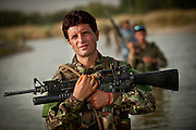 An Afghan National Army soldier wades in the Helmand River during a joint patrol in Sangin District, carrying a U.S.-made M-16 A2 with an M-203 grenade launcher.