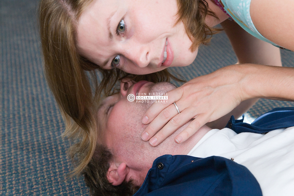 First Aid Officer at work carrying out CPR on an injured colleague and checking for signs of breathing,
