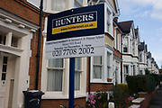 Local London Estate Agent Hunters, advertises a school Chrostmas fete with a mention on their housing placard.  Looking upwards to the sign, we see beyond and stretching into the distance a row of Victorian terraced homes in the south London suburb of Herne Hill, Lambeth SE24, approximately 5 miles south of the river Thames. As a piece of local PR, the company likes to be viewed as helping the neighbourhood by sponsoring events such as this Christmas market in the nearby school.