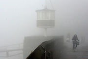 © Licensed to London News Pictures. 11/12/2013. London, UK. A woman cycles past a lookout point at a rowing club. Fog along the banks of the River Thames in Hammesmith, West London this morning 11th December 2013 . Photo credit : Stephen Simpson/LNP