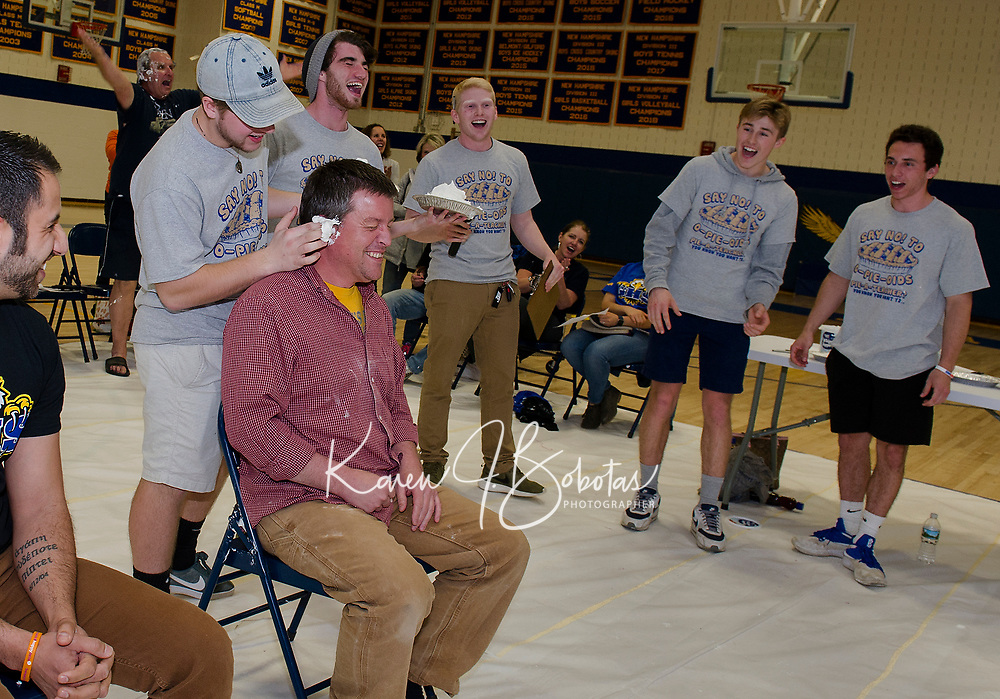 "Leaman Antone waits for his turn while Tyler Pearson starts with a little ""pie"" in the ears of Jason Javalgi during the ""Pie a Teacher"" fundraiser to benefit The Doorway at LRGH at Gilford High School on Friday.  (Karen Bobotas/for the Laconia Daily Sun)"