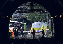 © Licensed to London News Pictures. 10/11/2016. Croydon, UK. Police and transport workers surround the overturned tram near Sandilands station. Investigations are continuing into a tram crash that police say claimed seven lives and injured 50. The driver has been arrested and is being questioned by police. Photo credit: Peter Macdiarmid/LNP
