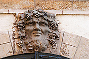 A sculpture of baccus bacchus baccus with beard and bunches of grapes and vine leaves in the hair as the headstone keystone key head of a vaulted door, the symbol of the Maison Jadot, Maison Louis Jadot, Beaune Côte Cote d Or Bourgogne Burgundy Burgundian France French Europe European