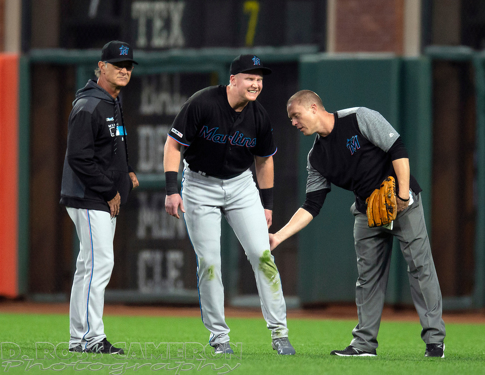 Sep 13, 2019; San Francisco, CA, USA; Miami Marlins right fielder Garrett Cooper, center, limps off the field after injuring himself diving for a line drive by San Francisco Giants Mike Yastrzemski during the first inning of a baseball game at Oracle Park. Miami Marlins manager Don Mattingly (8) is at left. Trainer is unidentified. Mandatory Credit: D. Ross Cameron-USA TODAY Sports