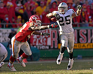Oakland Raiders running back Justin Fargas (25) works around Kansas City defender Keyaron Fox (97) in the fourth quarter at Arrowhead Stadium in Kansas City, Missouri, November 19, 2006.  The Chiefs beat the Raiders 17-13.<br />