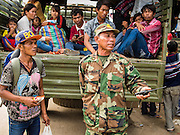 16 JUNE 2014 - POIPET, CAMBODIA: A Cambodian soldier helps returning Cambodian migrants get back to their home villages after the migrants returned to Cambodia Monday. More than 150,000 Cambodian migrant workers and their families have left Thailand since June 12. The exodus started when rumors circulated in the Cambodian migrant community that the Thai junta was going to crack down on undocumented workers. About 40,000 Cambodians were expected to return to Cambodia today. The mass exodus has stressed resources on both sides of the Thai/Cambodian border. The Cambodian town of Poipet has been over run with returning migrants. On the Thai side, in Aranyaprathet, the bus and train station has been flooded with Cambodians taking all of their possessions back to Cambodia.  PHOTO BY JACK KURTZ