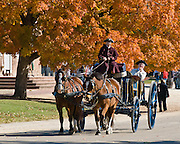 "An actor playing the wealthy Printer is carried in a two-horse carriage with driver, on Duke of Gloucester Street in Colonial Williamsburg. Colonial Williamsburg is the historic district of the independent city of Williamsburg, Virginia, which was colonial Virginia's capital from 1699 to 1780, and a center of education and culture. The capital straddled the boundary of two of the original shires of Virginia, James City Shire (now James City County), and Charles River Shire (now York County). Here, Thomas Jefferson, Patrick Henry, James Monroe, James Madison, George Wythe, Peyton Randolph, and dozens more helped mold democracy in the Commonwealth of Virginia and the United States. Motto: ""that the future may learn from the past.""  The Historic Area exhibits colonial houses and American Revolutionary War history. Prominent buildings in Colonial Williamsburg include the Raleigh Tavern, the Capitol, The Governor's Palace, and Bruton Parish Church. Interpreters work, dress, and talk as they did in the era, teaching visitors. The 301-acre Historic Area is located immediately east of the College of William and Mary, which was founded at Middle Plantation in 1693. The new College, long a desire of the colonists, was a key factor in the establishment of the town as capital of Virginia in 1698 and its renaming for King William III of England shortly thereafter.  Jamestown and Yorktown, the other two points of the Historic Triangle, are linked to Colonial Williamsburg by the National Park Service's bucolic Colonial Parkway."