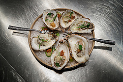 Oysters with Garlic, Parmesan and Guanciale (pork jown bacon). Atico, Fort Worth, Texas, USA. Atico is a Spanish tapas bar atop a Stockyards hotel and is owned by Tim Love.