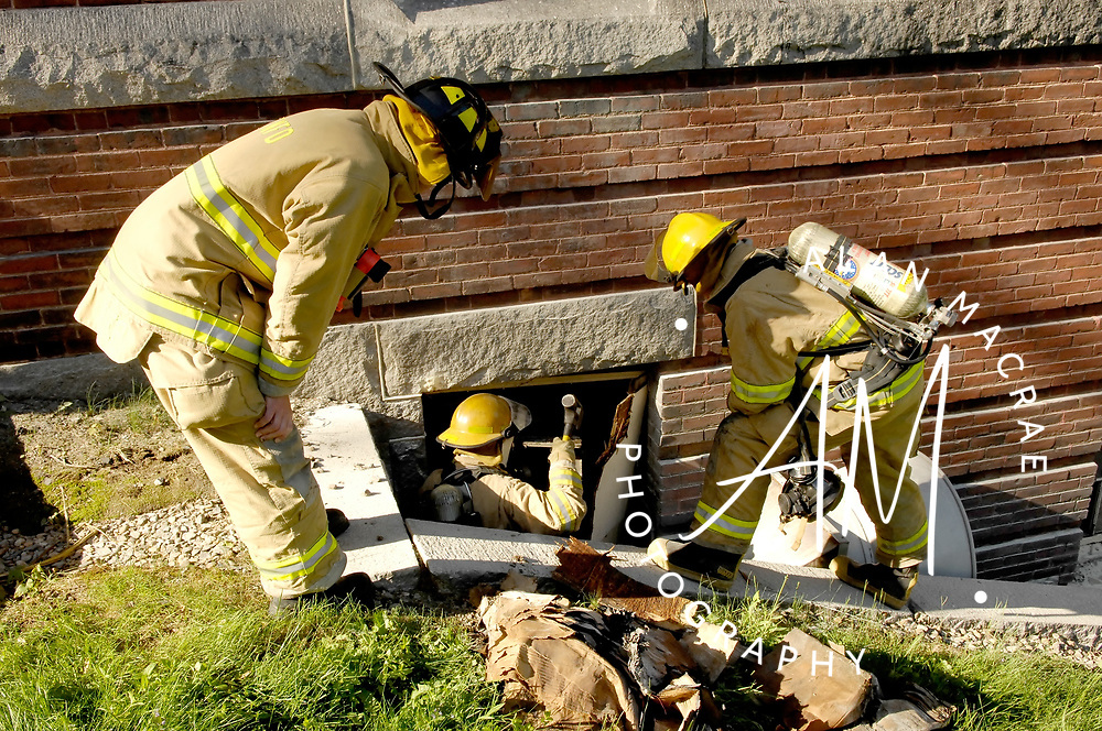 Tilton-Northfield firefighters look for hot spots in a wall at a Tilton School building early Tuesday morning.  The fire initially prompted a call for a first alarm, but was quickly brought under control.  The cause of the fire is under investigation by Tilton-Northfield Fire Prevention Officer Captain Brad Ober.  (Alan MacRae/for the Citizen)
