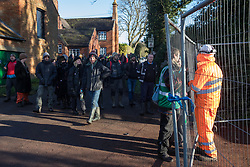 Harefield, UK. 18 January, 2020. Activists from Extinction Rebellion, Stop HS2 and Save the Colne Valley walk down Dews Lane towards a public footpath leading to Stop HS2's Harvil Road wildlife protection camp which had been fenced off by enforcement agents acting for HS2. They are attending a three-day 'Stand for the Trees' event timed to coincide with tree felling work by HS2. The enforcement agents have been evicting Stop HS2 activists from the camp for the past week and a half. 108 ancient woodlands are set to be destroyed by the high-speed rail link.