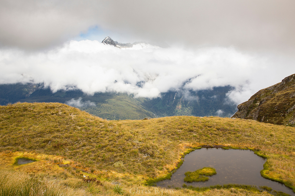 Mountain peak appearing through a break in the clouds, Routeburn Track, South Island, New Zealand