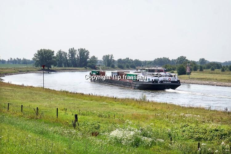 Nederland, Baak, 25-7-2019Een binnenvaartschip vaart over de IJssel beladen met containers. Foto: Flip Franssen