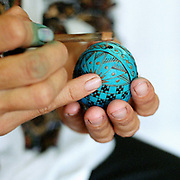 A woman applying molten wax to a blown egg using a tool called a kishitze (a stick with an iron tip), Hurghis, Bucovina, Romania. In Christian Orthodox countries such as Romania there is a tradition of skilfully painting eggs before Easter. After the pattern is applied the egg is then dipped in the lightest colour dye to be used. The egg is then heated and the protective wax melts away and a new pattern can be added, then dipped in a different colour and so on.